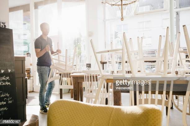 Man clearing cafe at closing time