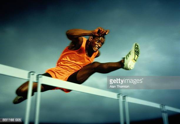 Man clearing hurdle, against grey sky (Digital Enhancement)