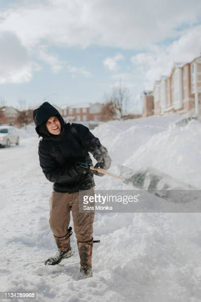 man clearing snow-covered road with shovel, toronto, canada - snow boot stock photos and pictures