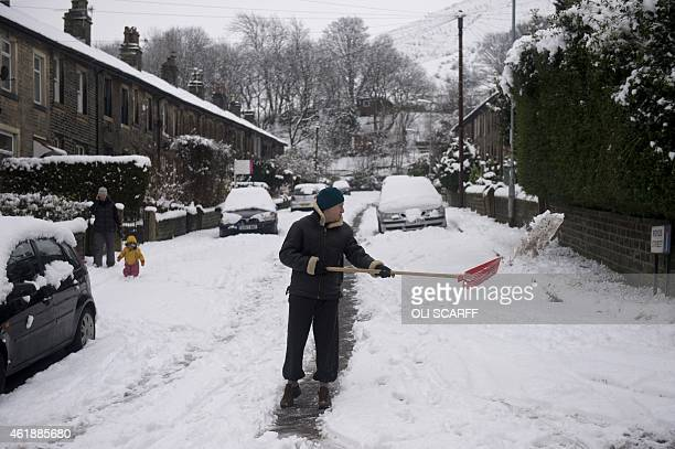 A man clears a route for vehicles to travel along a snowcovered residential street in the village of Marsden northern England on January 21 during...