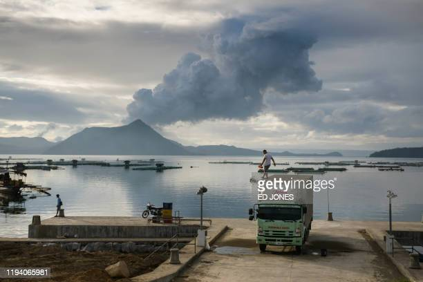 TOPSHOT A man clears ash from the roof of his truck before a plume of steam rising from the Taal volcano at a fishing harbour in Laurel on January 17...