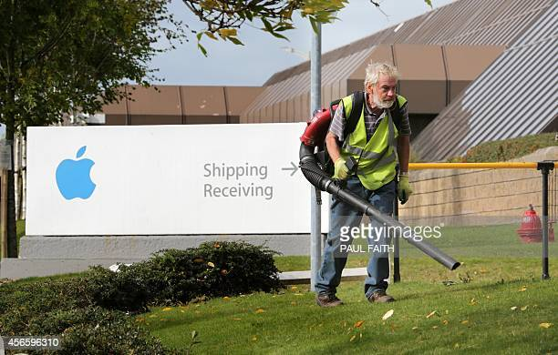 A man clears away leaves outside buildings on The Apple campus in Cork southern Ireland on October 2 2014 Perched on top of a hill overlooking the...