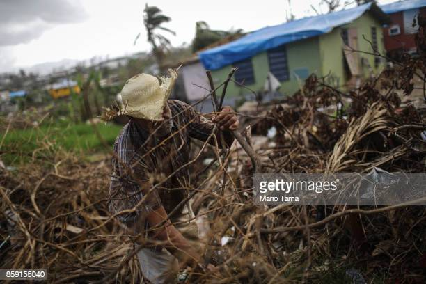 A man clears destroyed tree branches in a neighborhood without grid electricity more than two weeks after Hurricane Maria hit the island on October 8...