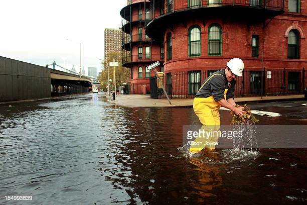 A man clears leaves from a sewer drain in lower Manhattan October 30 2012 in New York The storm has claimed at least 33 lives in the United States...