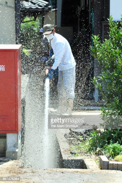 A man clears mud using sea water as water outage continues on July 13 2018 in Uwajima Ehime Japan The death toll from the torrential rain in western...