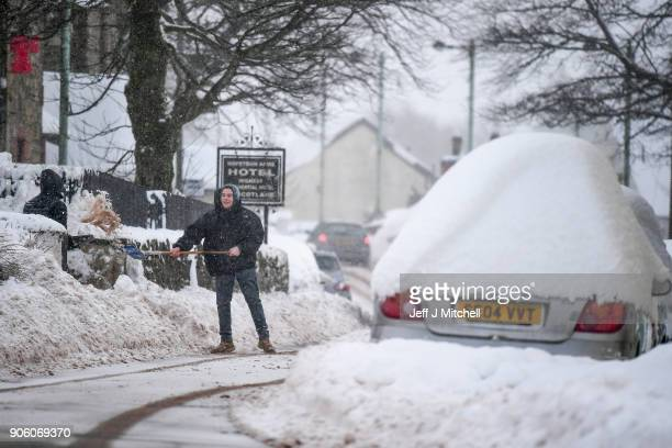 A man clears snow fall from his front door on January 17 2018 in Leadhills Scotland Motorist have been requested to avoid unnecessary journey on...