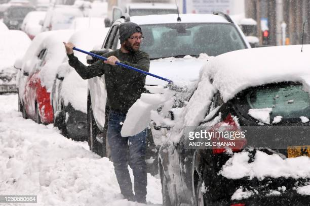 Man clears snow from his car in Auchterarder as heavy snow fell on parts of Scotland on January 14, 2021.