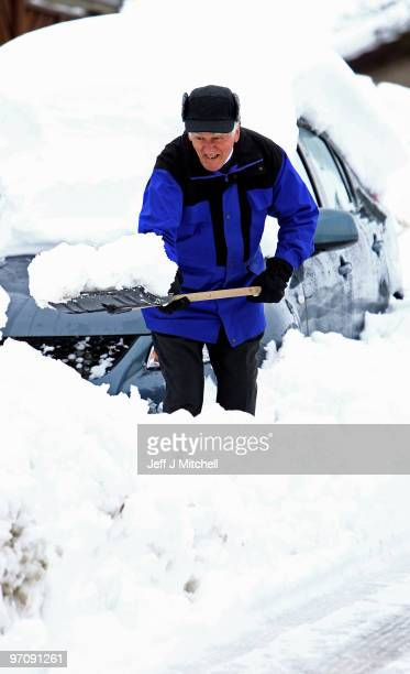 Man clears snow from his car in Auchterarder on February 26, 2010 in Auchtrerarder, Scotland. Homes in Scotland were left without power when...