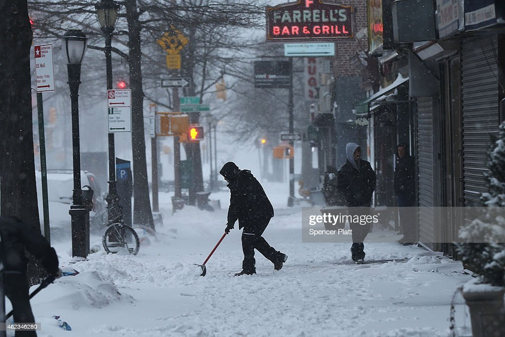 A man clears snow in Brooklyn the morning after a major winter storm on January 27, 2015 in New York City. Despite dire predictions, New York City was spared the worst of the storm, receiving up to a foot of snow in some areas. Subway buses were closed overnight while roadways were open only to emergency vehicles.