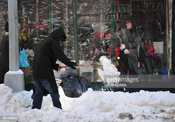 A man clears snow in front of a shop on Madison Avenue January 22 2014 in New York The northeastern US shivered amid heavy snowfall and far below...