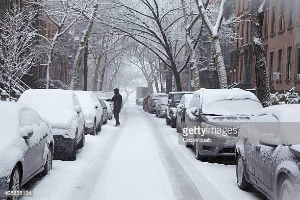 Man clears snow off car on Brooklyn Heights street
