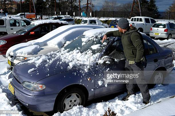 A man clears snow off his car parked at Katoomba train station on July 17 2015 in Katoomba Australia Snow has covered parts of New South Wales...