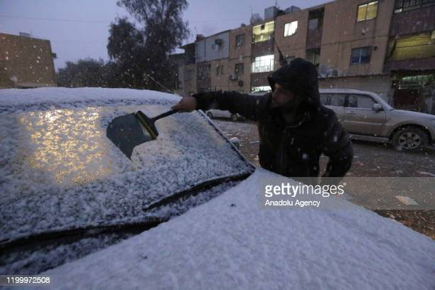 Man clears snow off of a car's window during snowfall in Baghdad, Iraq on February 11, 2020.