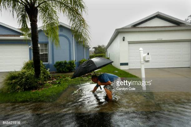 A man clears the drain next to his house in Estero Florida on Sunday Sept 10 2017 during the lull in winds as the eye of the hurricane passes over