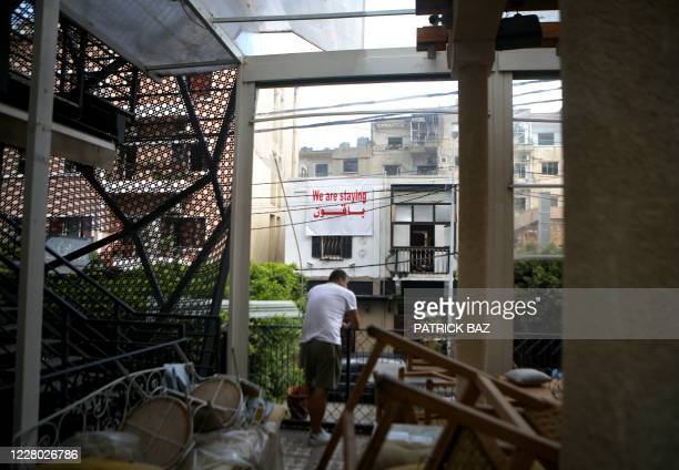 Man clears the rubble inside an apartment in the partially destroyed Beirut neighbourhood of Mar Mikhael on August 13 more than a week after a...