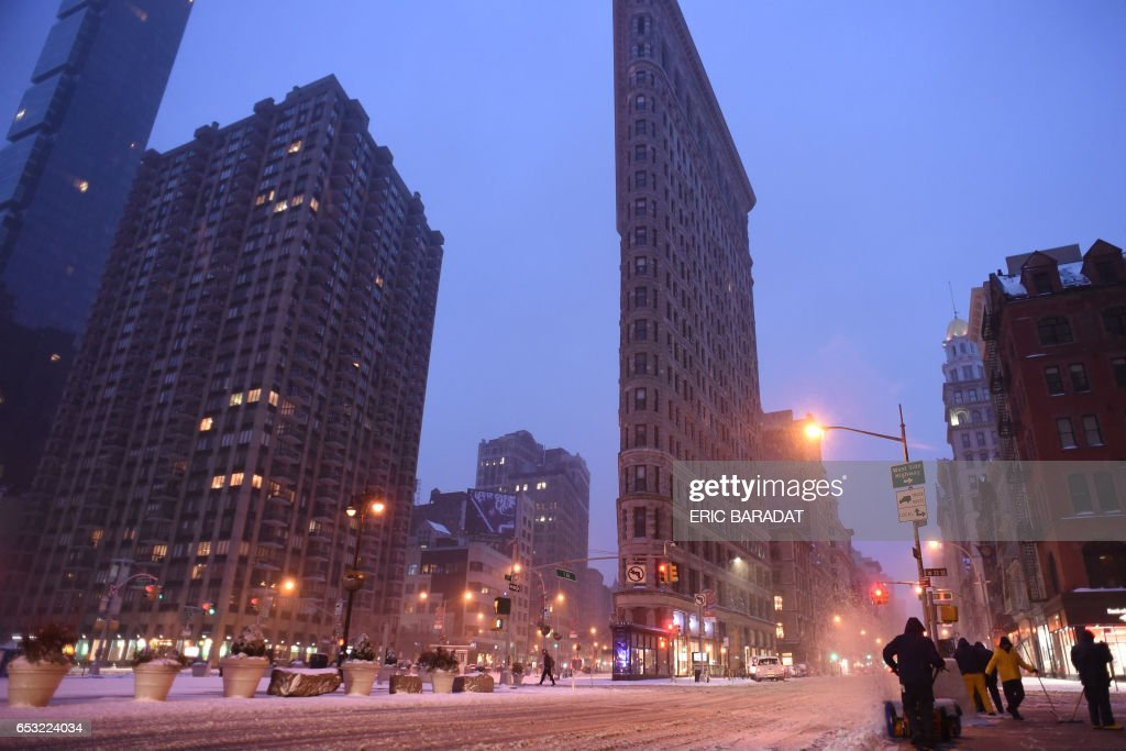 A man clears the sidewalk near Madison Square Park at the foot of the Flatiron building in Manhattan during a snowstorm in New York on March 14, 2017. Winter Storm Stella dumped snow and sleet Tuesday across the northeastern United States where thousands of flights were canceled and schools closed, but appeared less severe than initially forecast. After daybreak the National Weather Service (NWS) revised down its predicted snow accumulation for the city of New York, saying that the storm had moved across the coast. PHOTO / Eric BARADAT