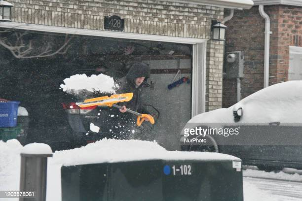 Man clears the snow from his driveway following a snowstorm in Toronto, Ontario, Canada, on February 27, 2020. The storm is dropped between 15-25...