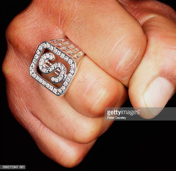 man clenching fist, 'dollar' sign ring on finger, close-up - bling bling stock pictures, royalty-free photos & images