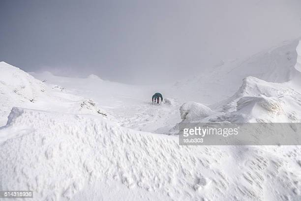 Man climbing a glacier coming up out of the clouds