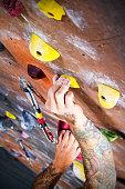 Man Climbing A Rock wall At An Indoor Gym