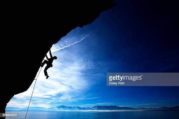 Man climbing against blue sky.