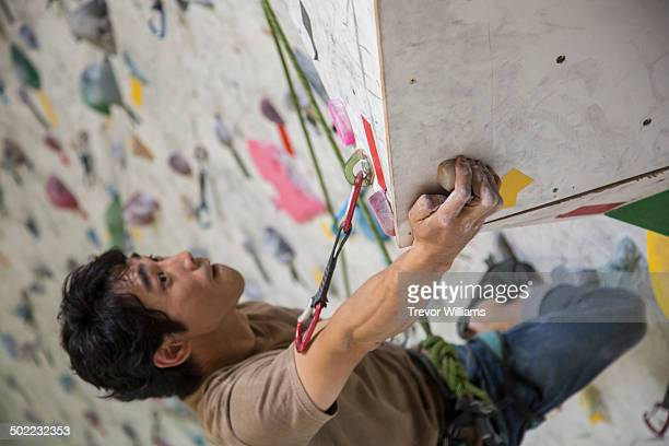 a man climbing at a rock climbing gym - スポーツ  ストックフォトと画像