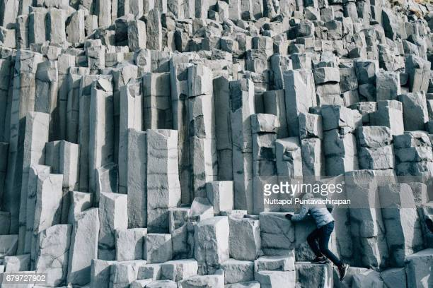 A Man Climbing Basalt Columns at Black Sand Beach in Iceland