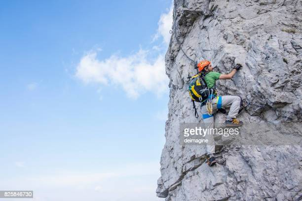 Man climbing equipped cliff