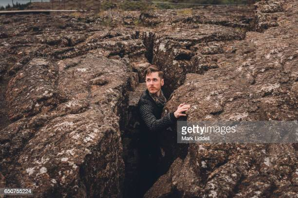 man climbing inside crevasse between tectonic plates in thingvellir national park, iceland - tectonic stock photos and pictures