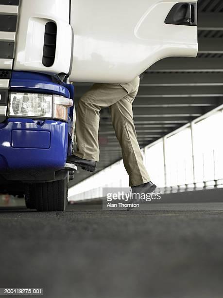 Man climbing into truck, ground view