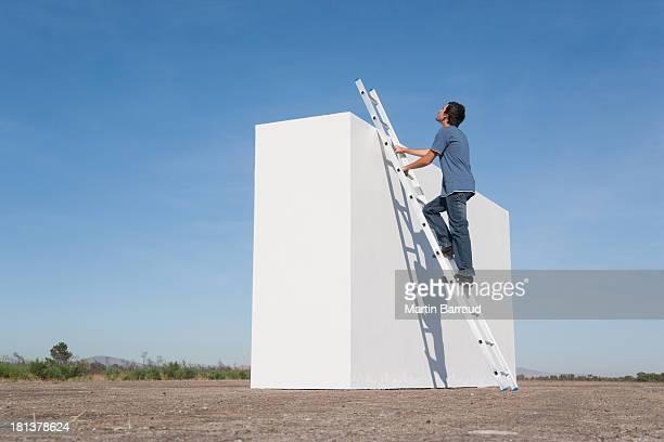 Homme escalade échelle contre le mur à l'extérieur