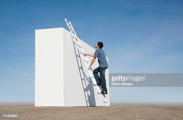 Man climbing ladder against wall outdoors