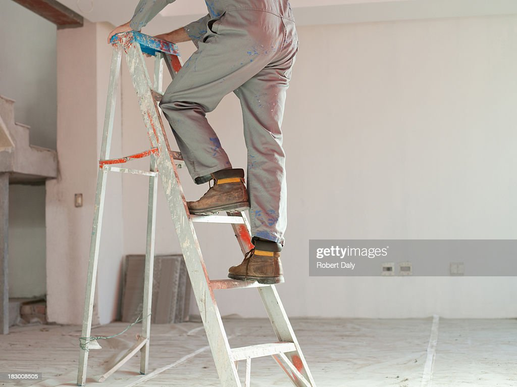 Man climbing ladder in unfinished room : Stock Photo