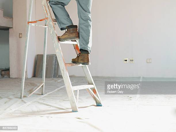 Man climbing ladder in unfinished room