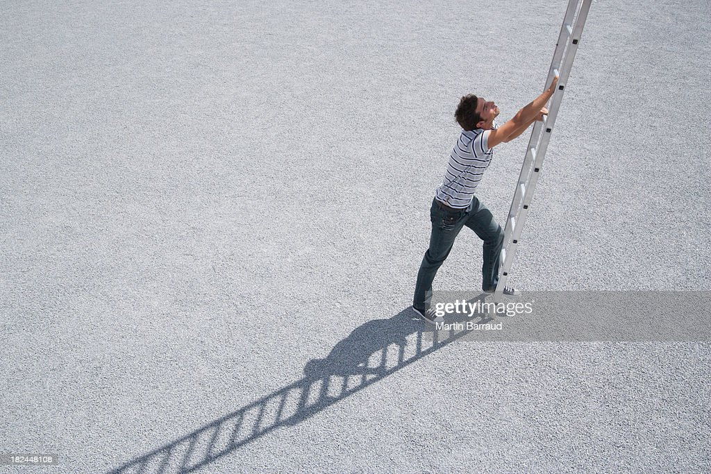 Man climbing ladder outdoors : Stock Photo