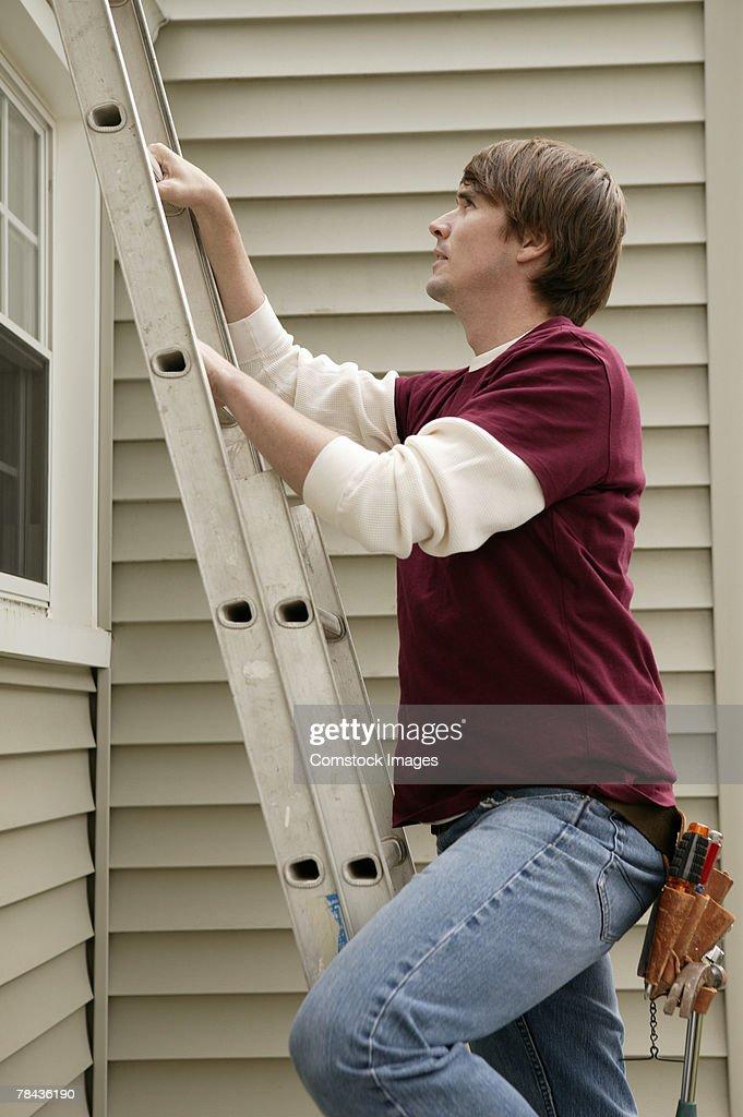 Man climbing ladder : Stockfoto