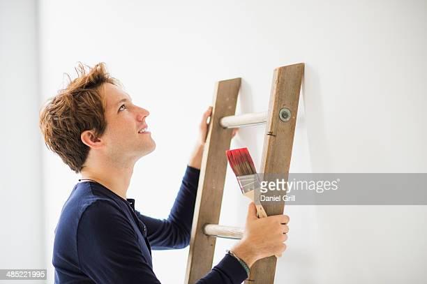 Man climbing ladder to paint wall