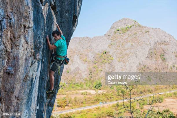 man climbing on limestone cliff in laos - bedrock stock pictures, royalty-free photos & images