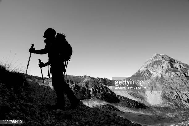 man climbing on mountain against clear sky during winter - andrea rizzi fotografías e imágenes de stock