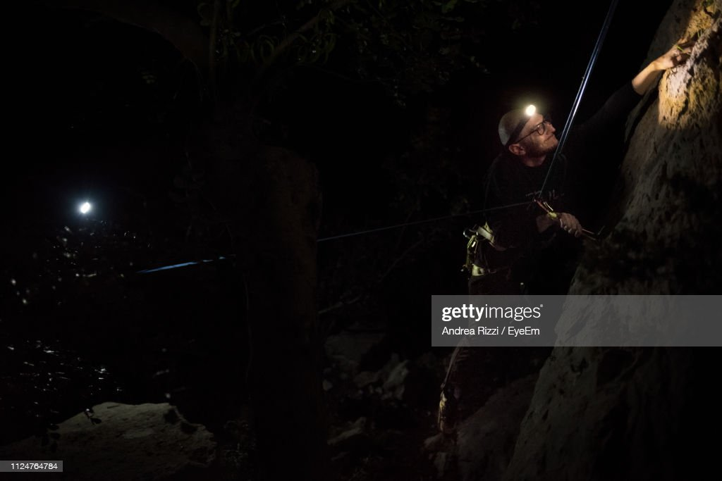 Man Climbing On Rock At Night : Foto stock