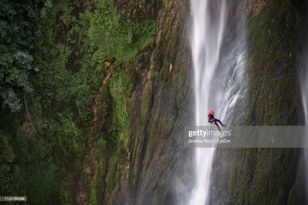 Man Climbing On Rock By Waterfall In Forest : Foto stock
