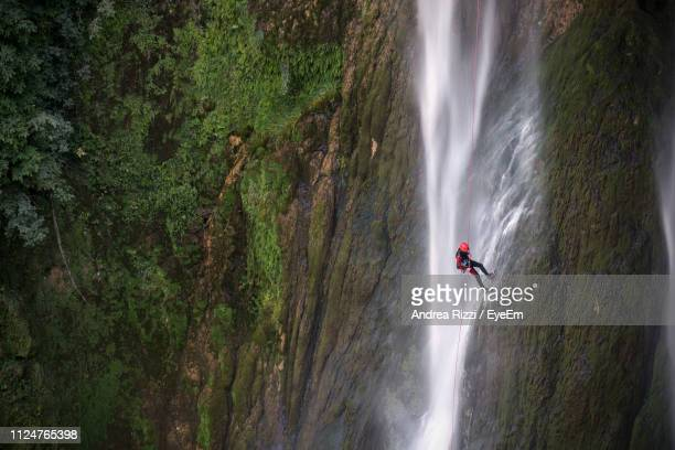 man climbing on rock by waterfall in forest - andrea rizzi stock pictures, royalty-free photos & images