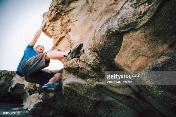 Man Climbing On Rock Formation Against Sky