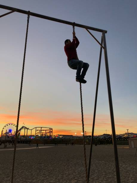 Man Climbing On Rope At Playground Against Sky During Sunset