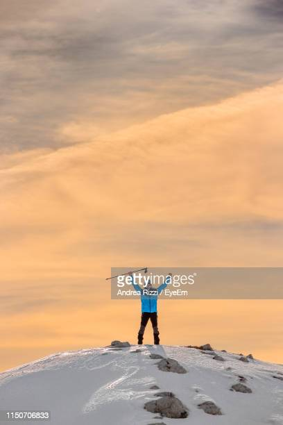 man climbing on snowcapped mountain against cloudy sky during sunset - andrea rizzi stock pictures, royalty-free photos & images