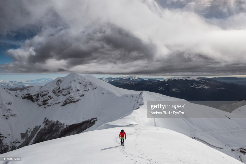 Man Climbing On Snowcapped Mountain Against Sky : Stock Photo