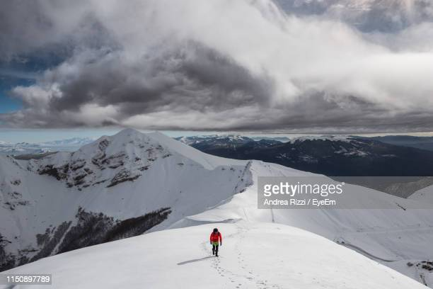 man climbing on snowcapped mountain against sky - andrea rizzi photos et images de collection