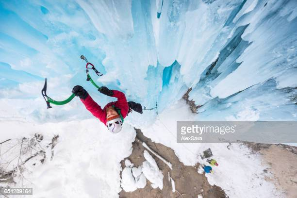 Man climbing on vertical frozen waterfall