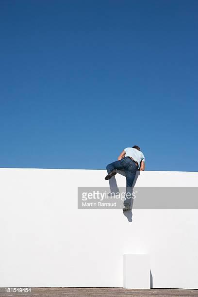 Mann Klettern an der Wand im Freien mit blauem Himmel