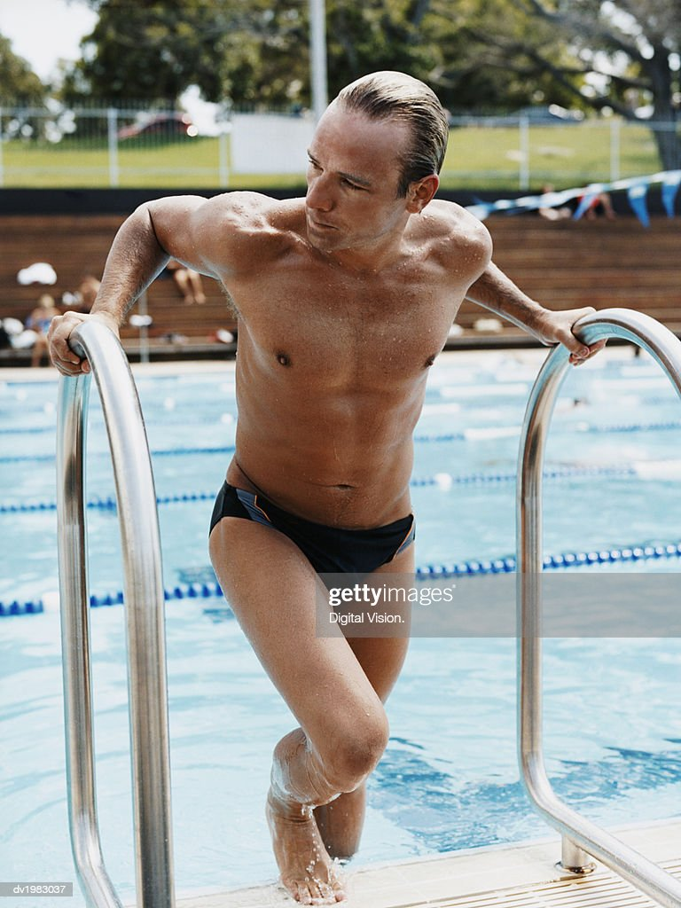 Man Climbing Out of a Swimming Pool : Stock Photo